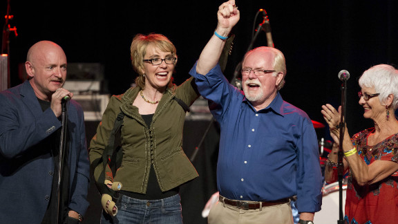 Former Arizona congresswoman Gabrielle Giffords holds hands with Arizona democratic congressional candidate Ron Barber at a campaign rally on Saturday.