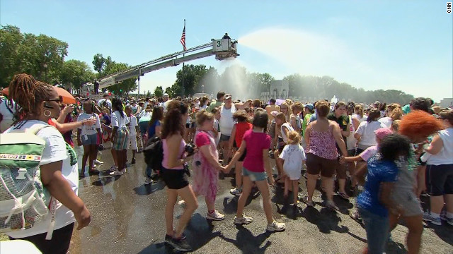 Girl Scouts at the National Mall take advantage of a fire department cooling station on Saturday.