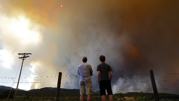 Robby Wood, left, of Denver and his 16-year-old nephew, Jacob Wood, watch the thick smoke rise over a hill near Laporte.