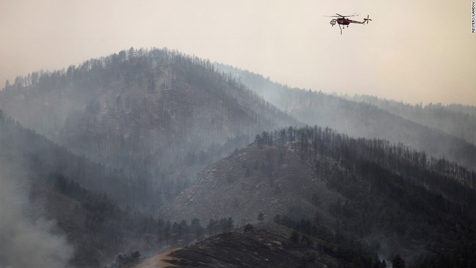 A firefighting helicopter surveys the High Park Fire for hot spots Sunday near Laporte as the wind-driven blaze spreads.
