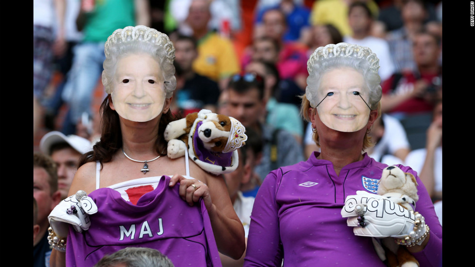 England fans wearing Queen Elizabeth II masks watch the match against France on Monday.