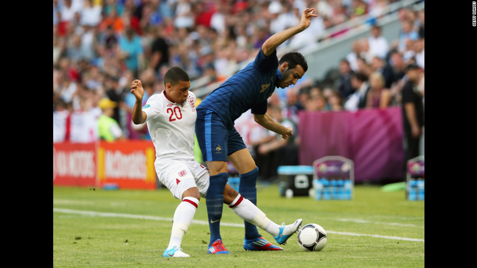 Alex Oxlade-Chamberlain of England and Adil Rami of France fight for possession.