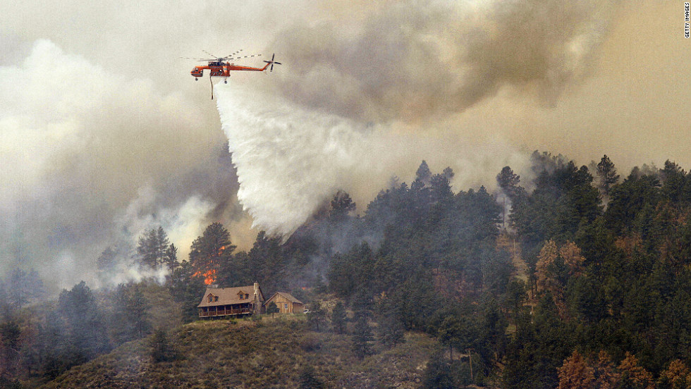 A helicopter drops water on a hot spot burning close to homes on Monday near Laporte, Colorado.