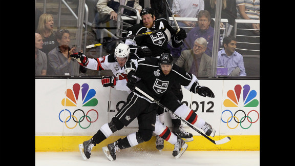 The Devils' Ryan Carter gets checked by Matt Greene and Jordan Nolan of the Kings in the first period.