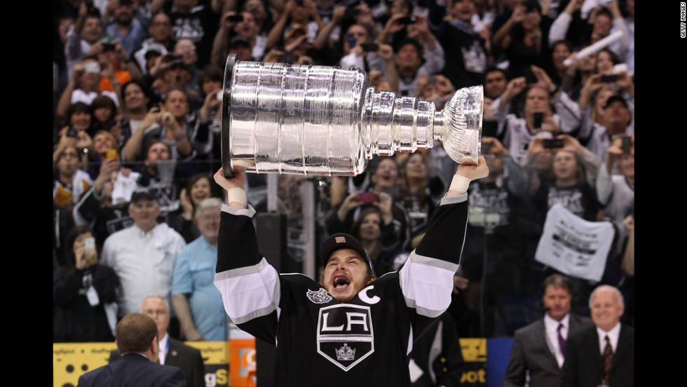 Captain Dustin Brown of the Los Angeles Kings holds up the Stanley Cup after his team defeated the New Jersey Devils 6-1 on Monday, June 11.