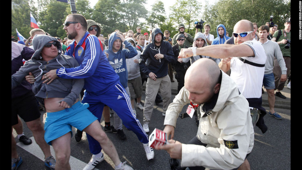 A Polish journalist, second right, is beaten by football fans in Warsaw.