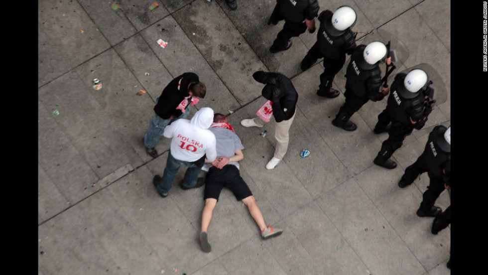 An injured polish soccer fan lies on the ground.