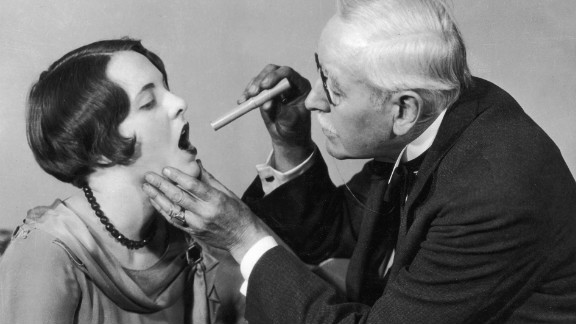 A doctor examines the throat of a young woman using a small pen light  around 1927.