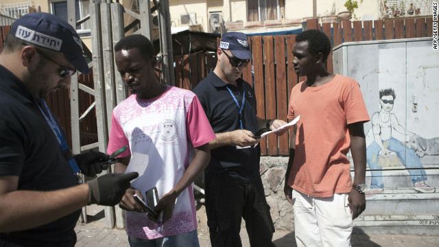 Israeli immigration officers check documents of South Sudanese migrants Tuesday in the southern Israeli city of Eilat.