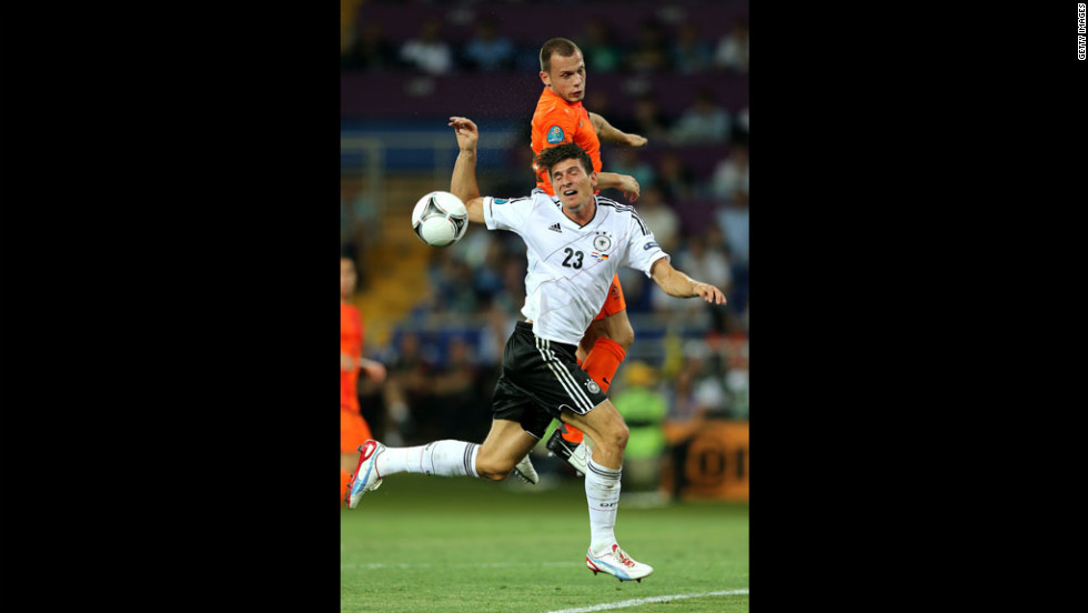John Heitinga of the Netherlands and Mario Gomez of Germany fight for the ball.
