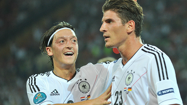 Germany striker Mario Gomez is congratulated by midfielder Mesut Oezil after scoring the first of his two goals