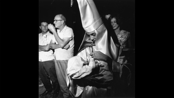 A woman dressed in Ku Klux Klan regalia holds her baby at a KKK meeting in Beaufort, South Carolina, in 1965.