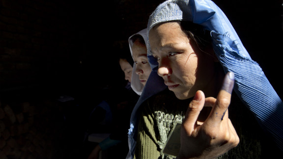 An Afghan woman shows off her ink-stained finger before casting a vote in Kabul in elections in September 2010.