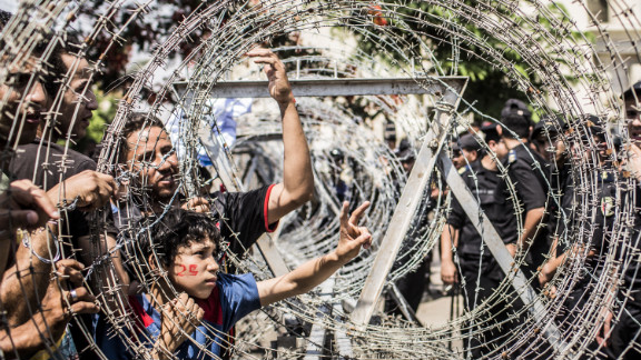 Protestors gesture towards military police through a barricade of barbed wire during a protest against presidential candidate Ahmed Shafik outside the Supreme Constitutional Court on Thursday.