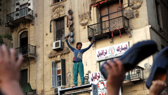 An Egyptian boy waves his shoes as he joins supporters of the Muslim Brotherhood in a protest in Cairo