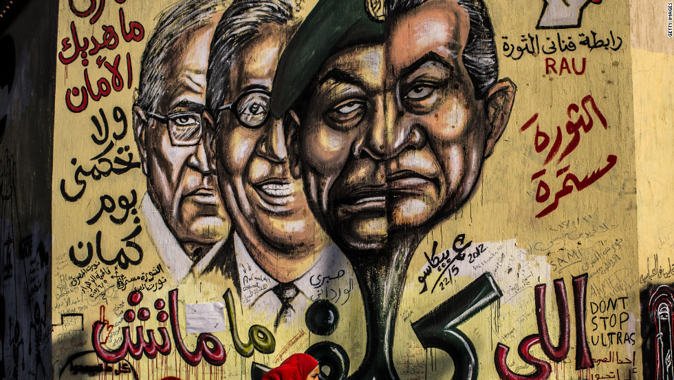 People Walk Past Graffiti Showing Faces Of Ousted Egyptian President Hosni Mubarak Right Field