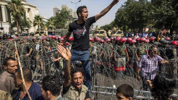 A protester stands on a barricade of barbed wire as Egyptian military police stand guard. Egypt