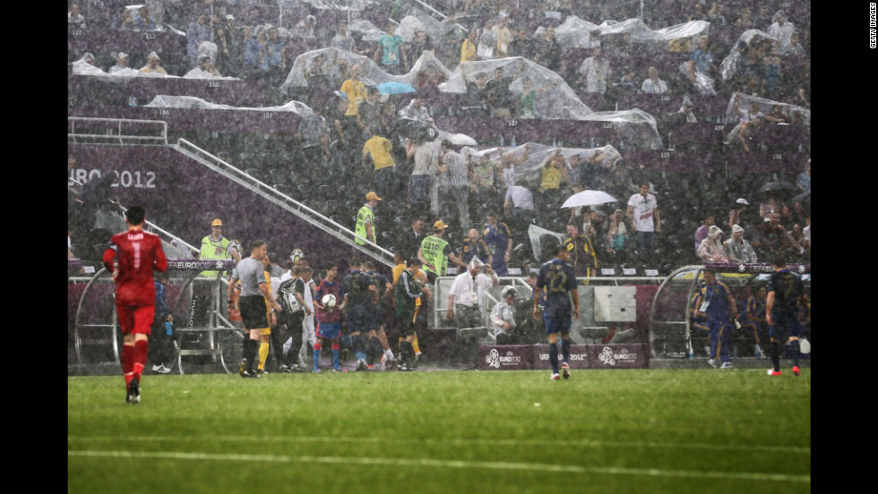 Players leave the field Friday after weather caused the Ukraine vs. France game to be suspended.