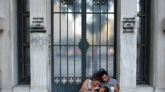 A family beg on the street in front of the National Bank in Athens. Greece is facing its fifth year of recession.