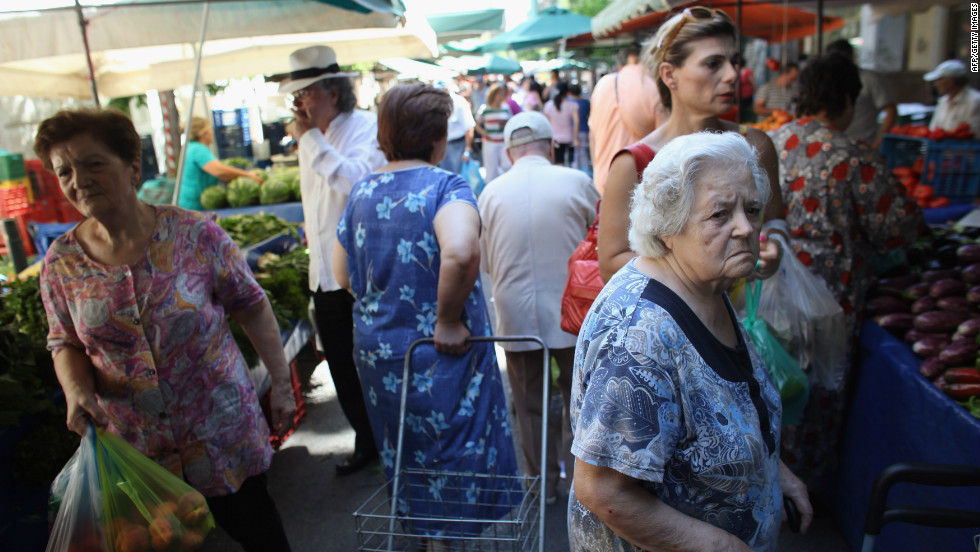 Greek people buy fruit and vegetables from a market in Omonoia on June 12, in Athens. After nearly three years of austerity measures, some Greeks say it is a struggle to continue feeding their families.