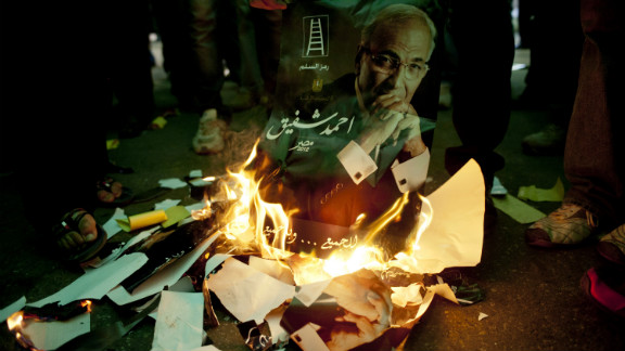 Egyptians burn the likeness of presidential candidate and former Prime Minister Ahmed Shafik in Cairo on Friday, the eve of the nation