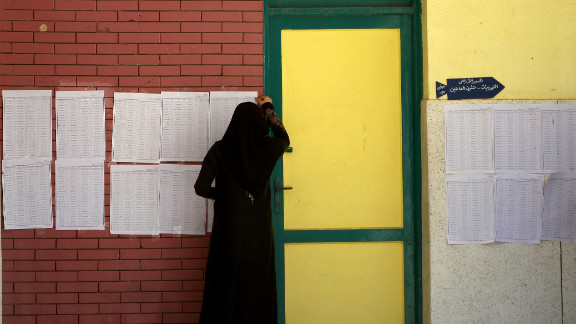 A veiled Egyptian woman looks for her name on the registered voters