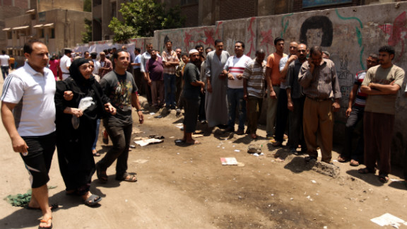 Egyptian Christian Coptic men help a woman reach a polling station in the Cairo Coptic Shubra neighborhood on Saturday, June 16.  Voters returned to the polls after Egypt