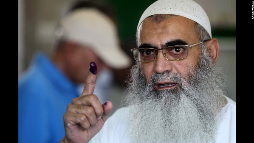 An Egyptian Muslim Salafist shows his ink-stained finger after voting at a polling station.