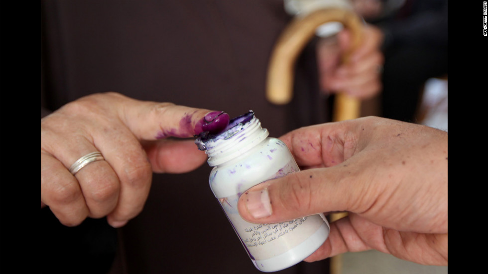 An Egyptian woman dips her finger in indelible ink after casting her ballot.