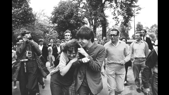"McCartney is hugged by an adoring fan after arriving at rehearsal for the TV show ""Jukebox Jury"" in London in 1964."