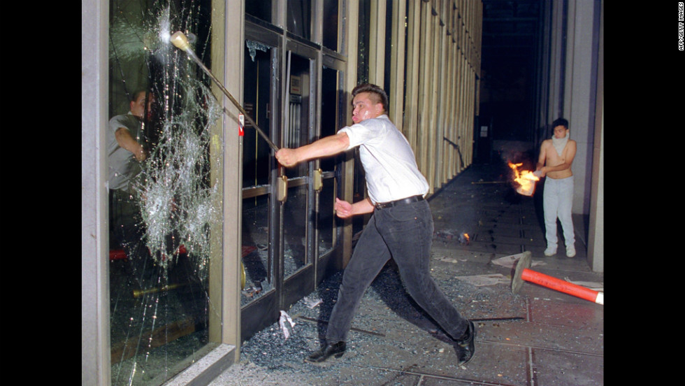 A rioter breaks a glass door of the Criminal Courts building in downtown Los Angeles on April 29.