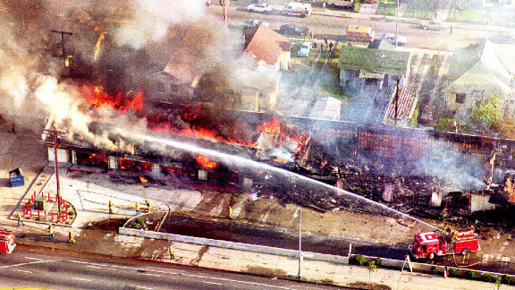 Firefighters spray water on a burning building in south Los Angeles on April 30, 1992, a day after rioting broke out over  the acquittal of four white police officers charged with assault and the use of excessive force on Rodney King.