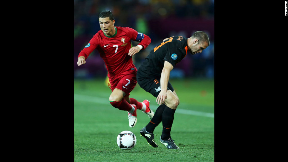 Cristiano Ronaldo of Portugal competes with Ron Vlaar of the Netherlands.
