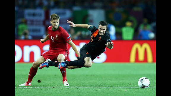 Miguel Veloso of Portugal challenges Robin van Persie of the Netherlands on Sunday.