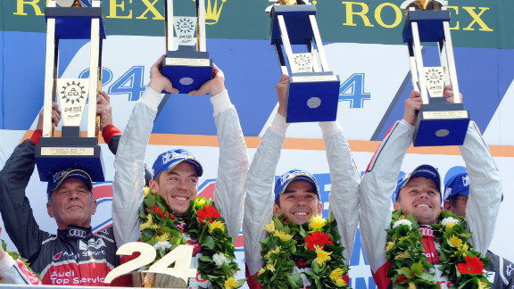 Audi motorsport director Dr. Wolfgang Ullrich, left, celebrates on the podium with his drivers after the team's victory in the 80th edition of the race.