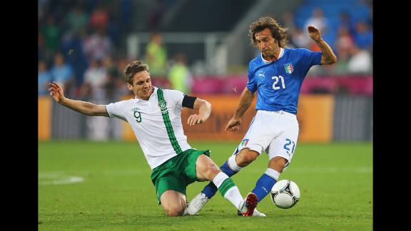 Kevin Doyle of Ireland tackles Andrea Pirlo of Italy.