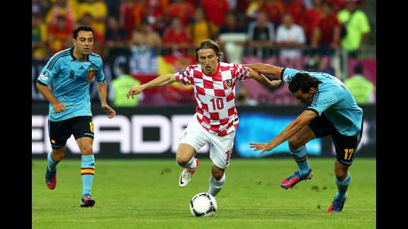 Luka Modric of Croatia is closed down by Alvaro Arbeloa and Xavi of Spain.