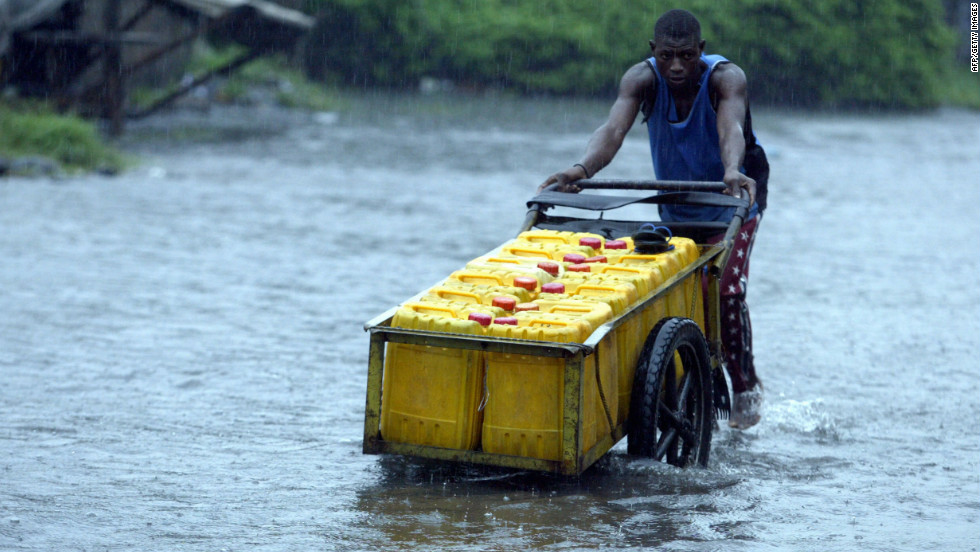 A man in Lagos wades through the aftermath of a heavy downpour in 2012.