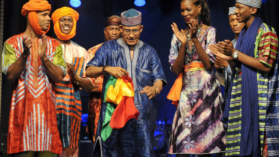 Models applaud Niger fashion designer Alphadi -- shown holding the Senegalese flag -- at the end of the opening day on June 12.