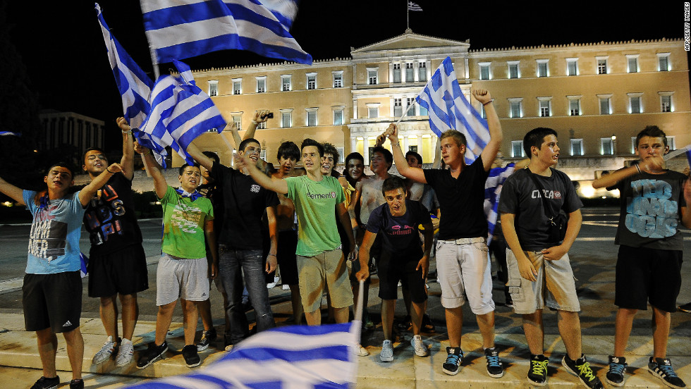 Greek football fans celebrate their win over Russia outside their parliament and on the eve of Sunday's key elections.