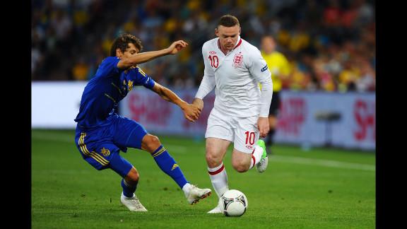 Wayne Rooney of England breaks past Denys Harmash of Ukraine during Tuesday
