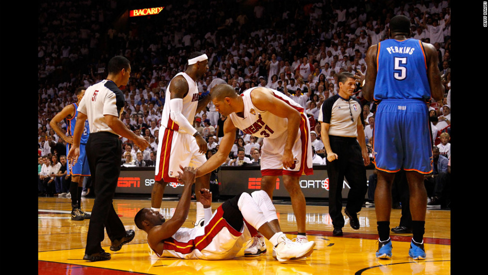 Dwyane Wade, No. 3 of the Heat, is helped up by teammate Shane Battier, No. 31, in the first quarter against the Thunder.