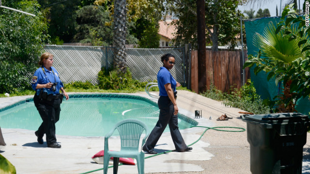 RIALTO, CA - JUNE 17: Detective Carla McCullough (R) with Rialto Police directs a police photographer as they investigate the death of Rodney King who was found in his pool on June 17, 2012 in Rialto, California. King, whose video beating by Los Angeles police in 1991 sparked riots after the acquittal of the four officers involved, was found dead at the age of 47 from an apparent drowning in his swimming pool. (Photo by Kevork Djansezian/Getty Images) *** BESTPIX ***