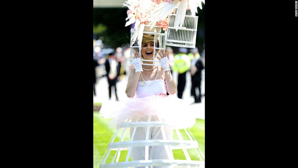 A woman wearing an elaborate hat designed to look like a bird cage attends day one of the races.