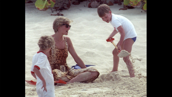 On a private beach in 1990, Prince William shovels sand onto his mother. Photos of the young prince with his adoring mother were common as media interest swelled.