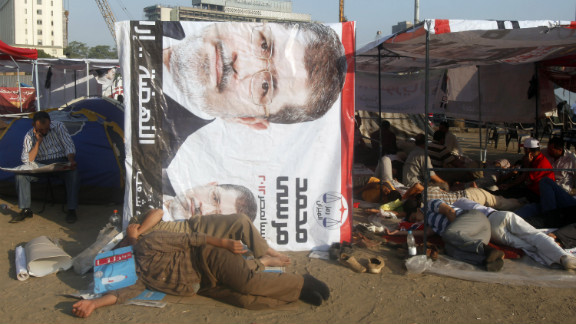 Egyptian activists rest at the foot of a banner of presidential candidate Mohamed Morsi in Cairo