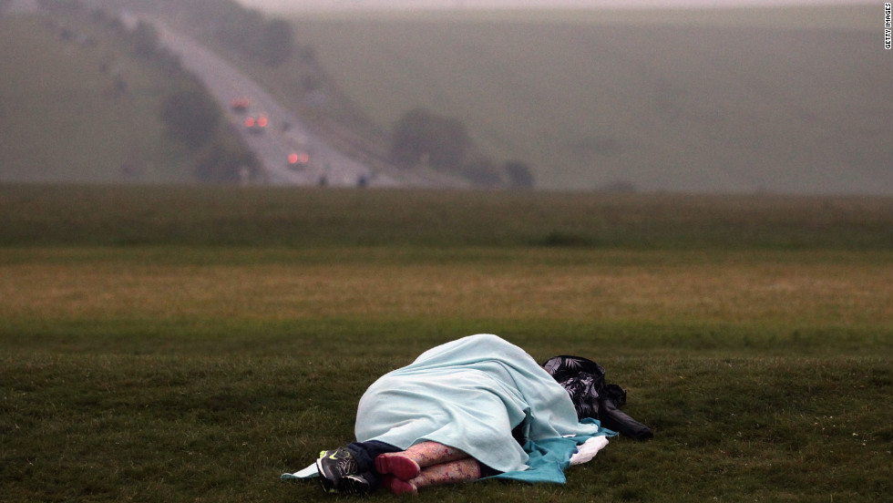 A couple sleeps in a field near Stonehenge early Thursday as revelers gather to celebrate the summer solstice.