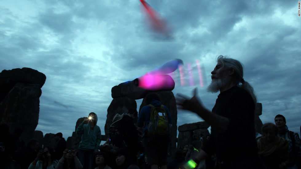 A man juggles glowing batons as others take pictures to commemorate the solstice.