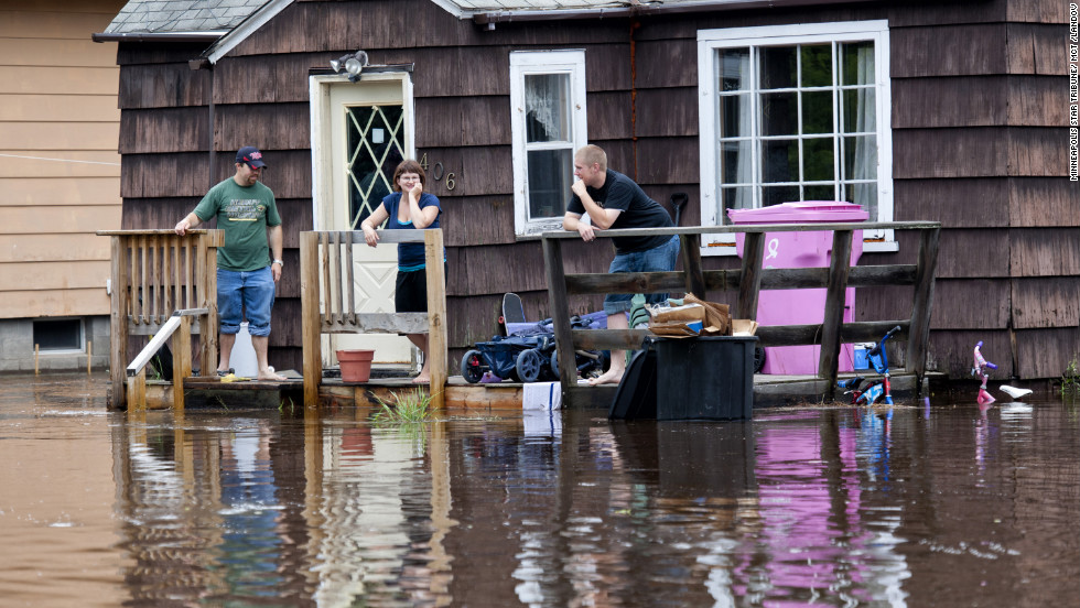 Friends of Tyler Dewsbury wait for help Wednesday so they can move belongings from his flooded house in Carlton, southwest of Duluth.