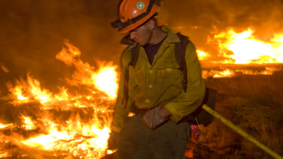 Photographer Kari Greer has spent years documenting wildfires and firefighters in much of the United States. In this photo, a firefighter works a low-intensity burn operation June 14 at Lincoln National Forest in New Mexico.